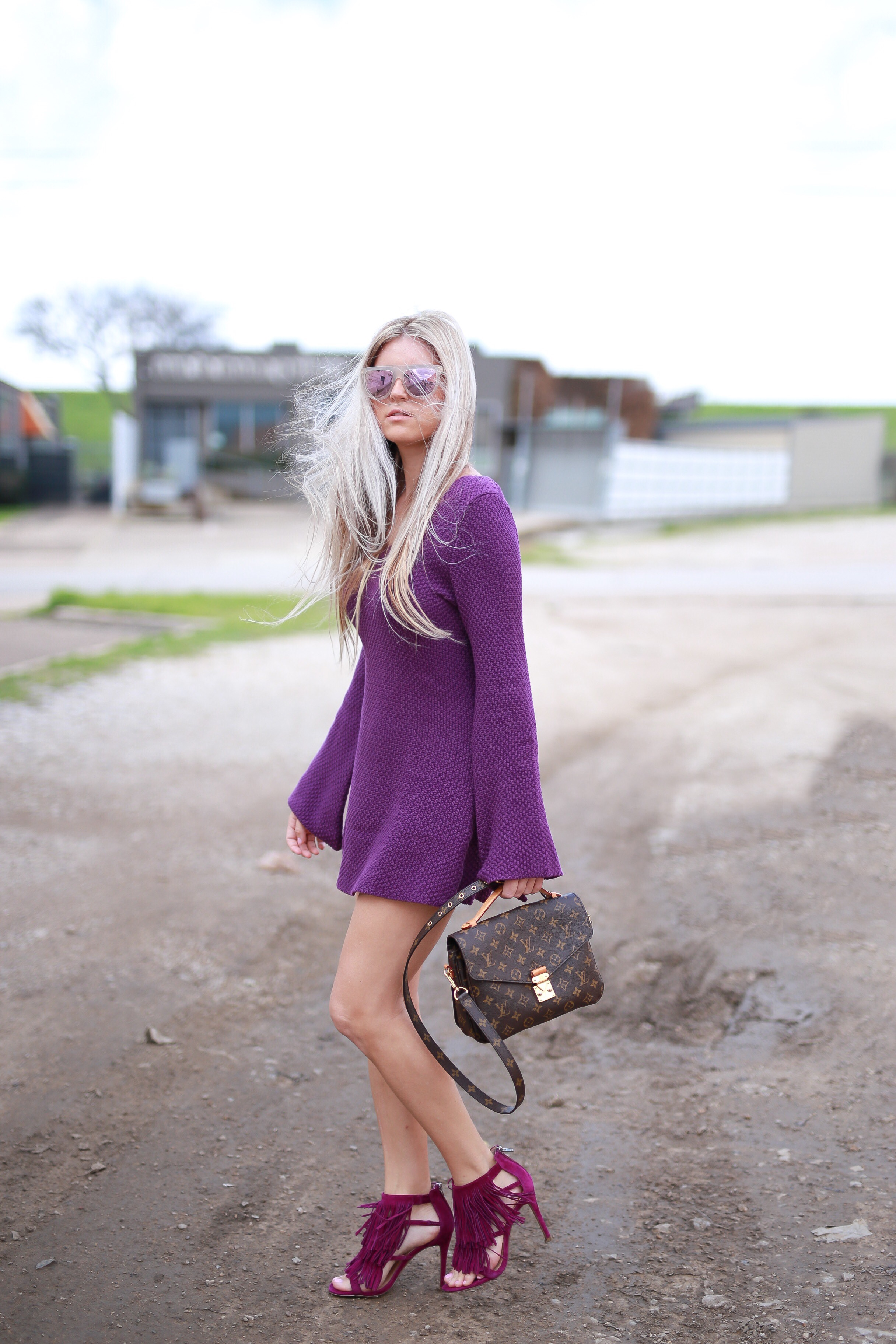 Stephany Bowman Editor of Stephany's Choice wearing a purple bell sleeve knit dress from TOBI, sunglasses from HENRI BENDEL New York, messenger bag from Louis Vuitton and Purple fringe high heels from Steve Madden