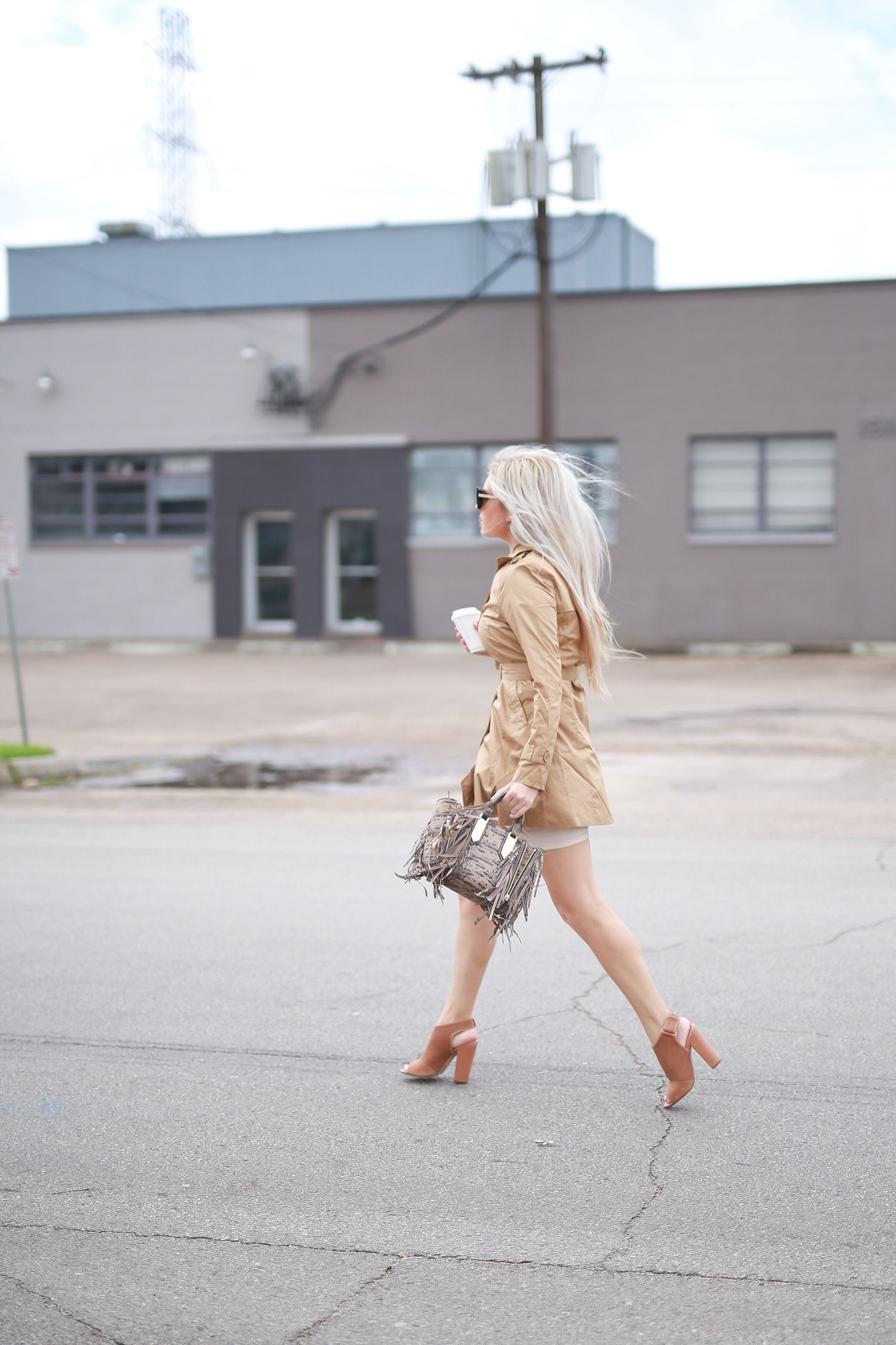 Stephany Bowman , Editor of Stephany's Choice, wearing a cream trench from TOBI, heels from Aldo , Sunglasses and snakeskin fringed bag from Henri Bendel