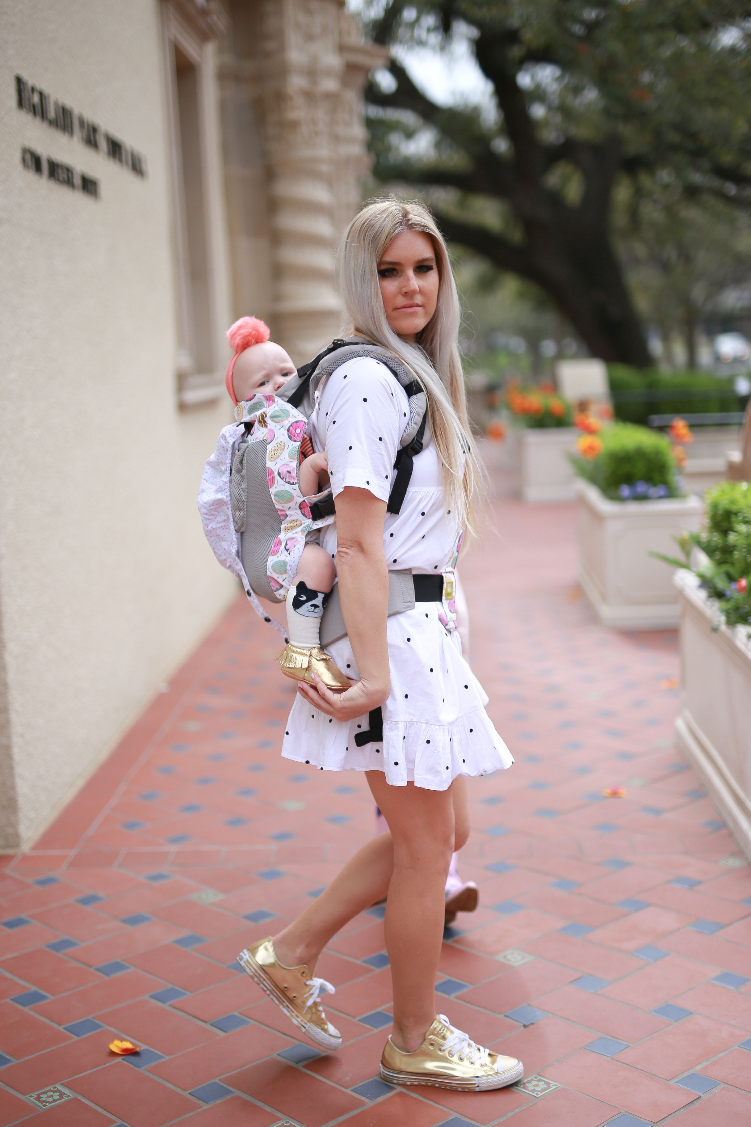 Stephany Bowman, Editor of Stephany's Choice wearing a white polka-dot ZARA smocked dress, Gold CONVERSE shoes, and baby carrier from LILLE . Angelina Bowman wearing OLLIE AND MAE