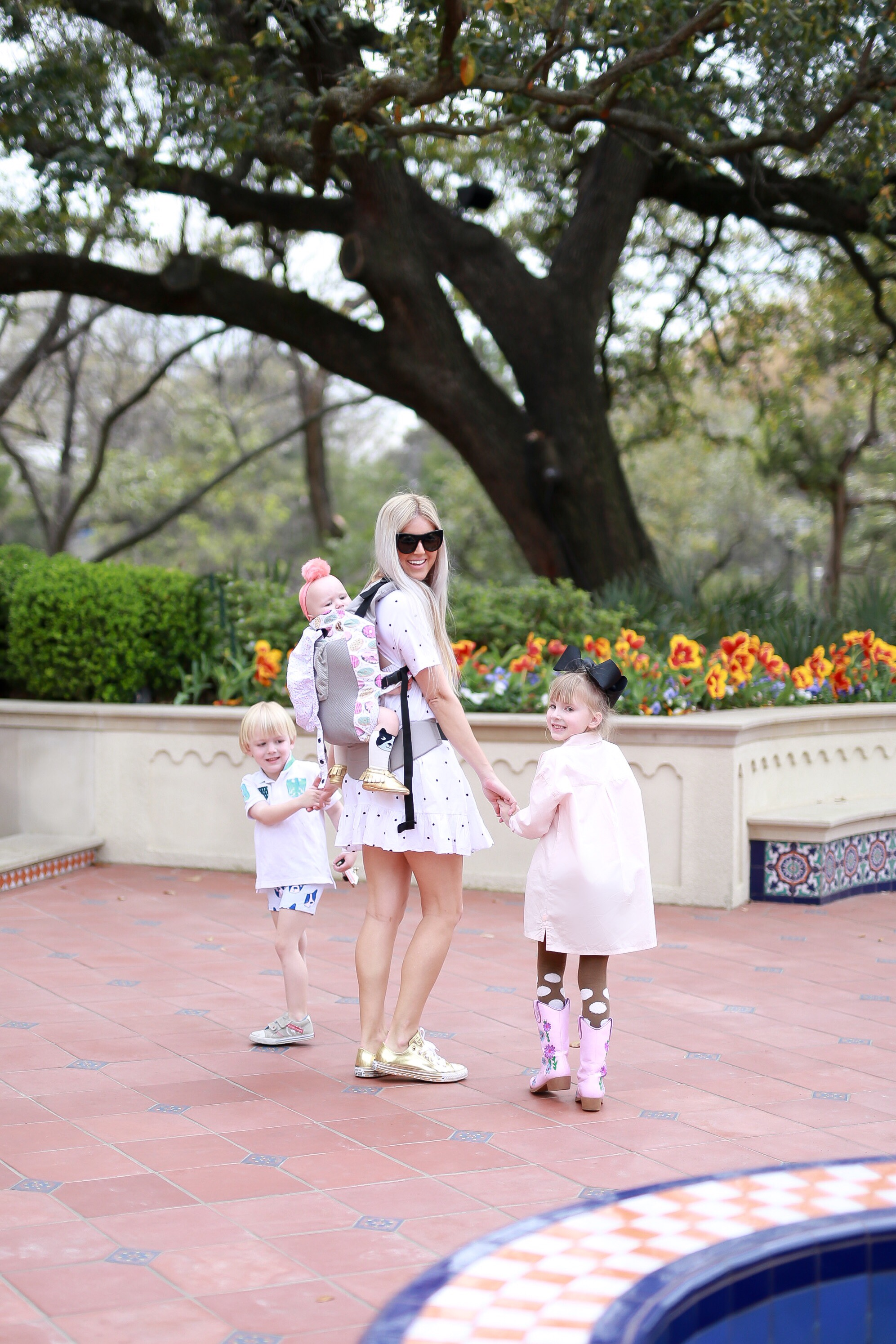 Stephany Bowman wearing a white polka dot, short smocked dress from ZARA. Gold sneakers from CONVERSE, and Black cat eye sunglasses from HENRI BENDEL. Annabelle, Alexander and Angelina Bomwan wearing outfits from Children's Boutique OLLIE AND MAE