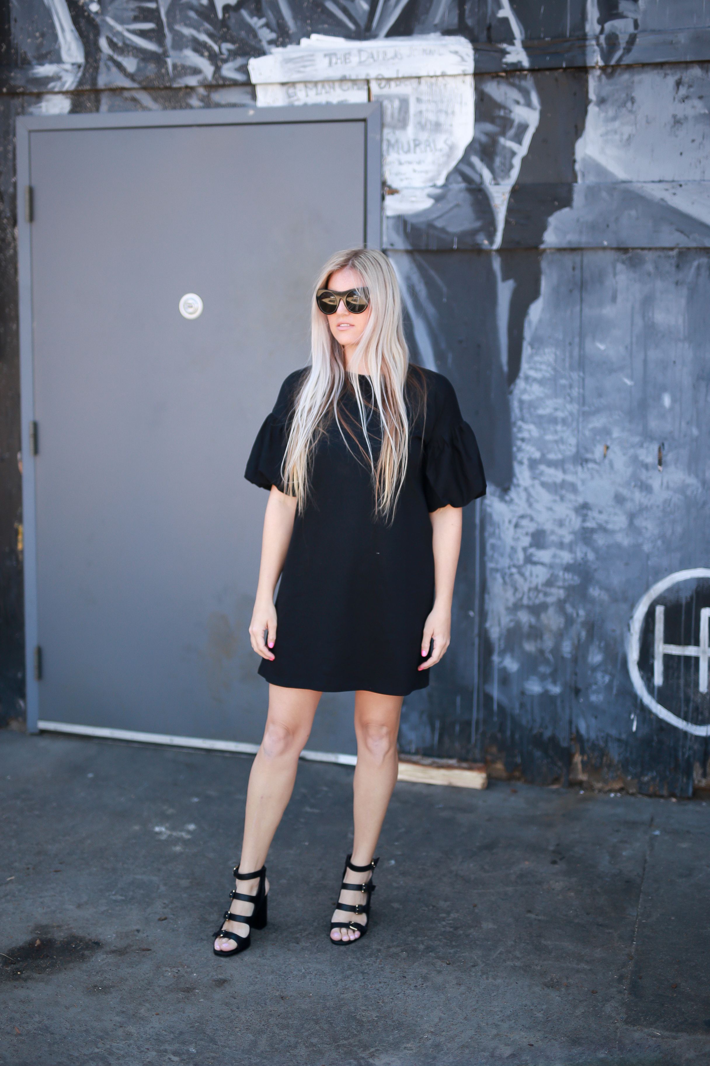 Stephany Bowman Editor of Stephany's Choice wearing ZARA black jersey dress, black buckle ALDO heels and Cat eye HENRI BENDEL sunglasses