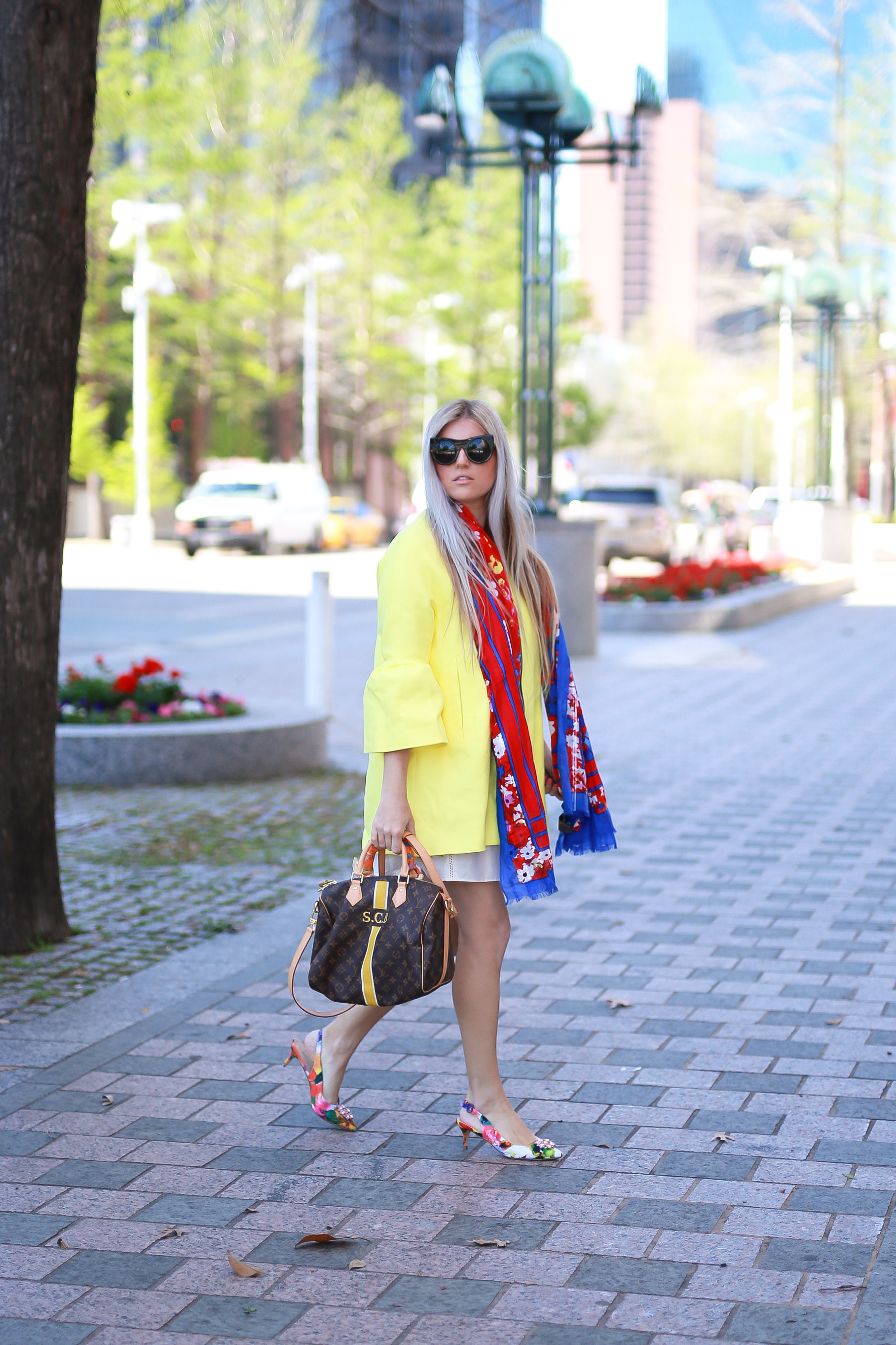 Stephany Bowman Editor of Stephany's Choice wearing a yellow zip up, bell sleeve jacket and printed red scarf from ZARA, black cat eye sunglasses from Louis Vuitton, and personalized Speedy bag from Louis Vuitton