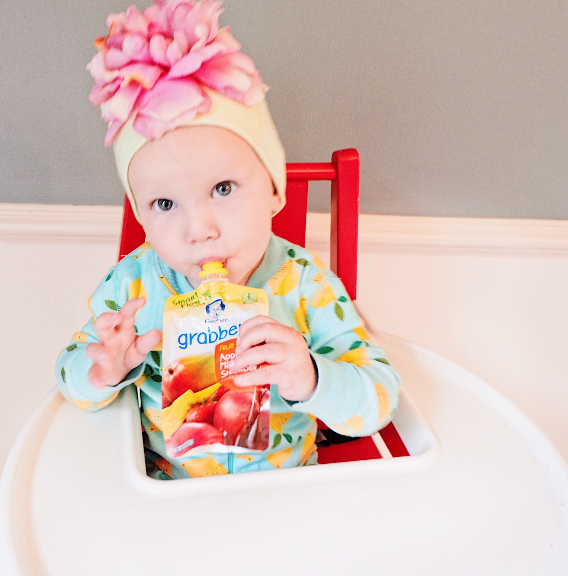 Angelina Bowman wearing a Hanna Anderson onesie in lemon print and snacking on a Gerber ®️Smart Flow ™️