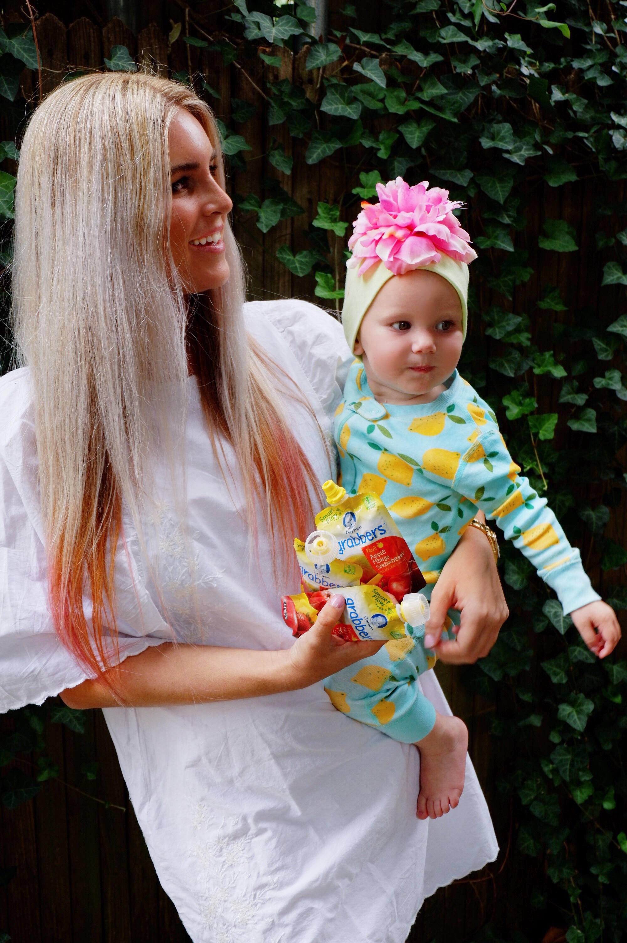 Stephany Bowman wearing a ZARA white dress, Angelina Bowman wearing a Hanna Anderson lemon onesie and snacking on GERBER ®️ SMART FLOW ™️ toddler pouches