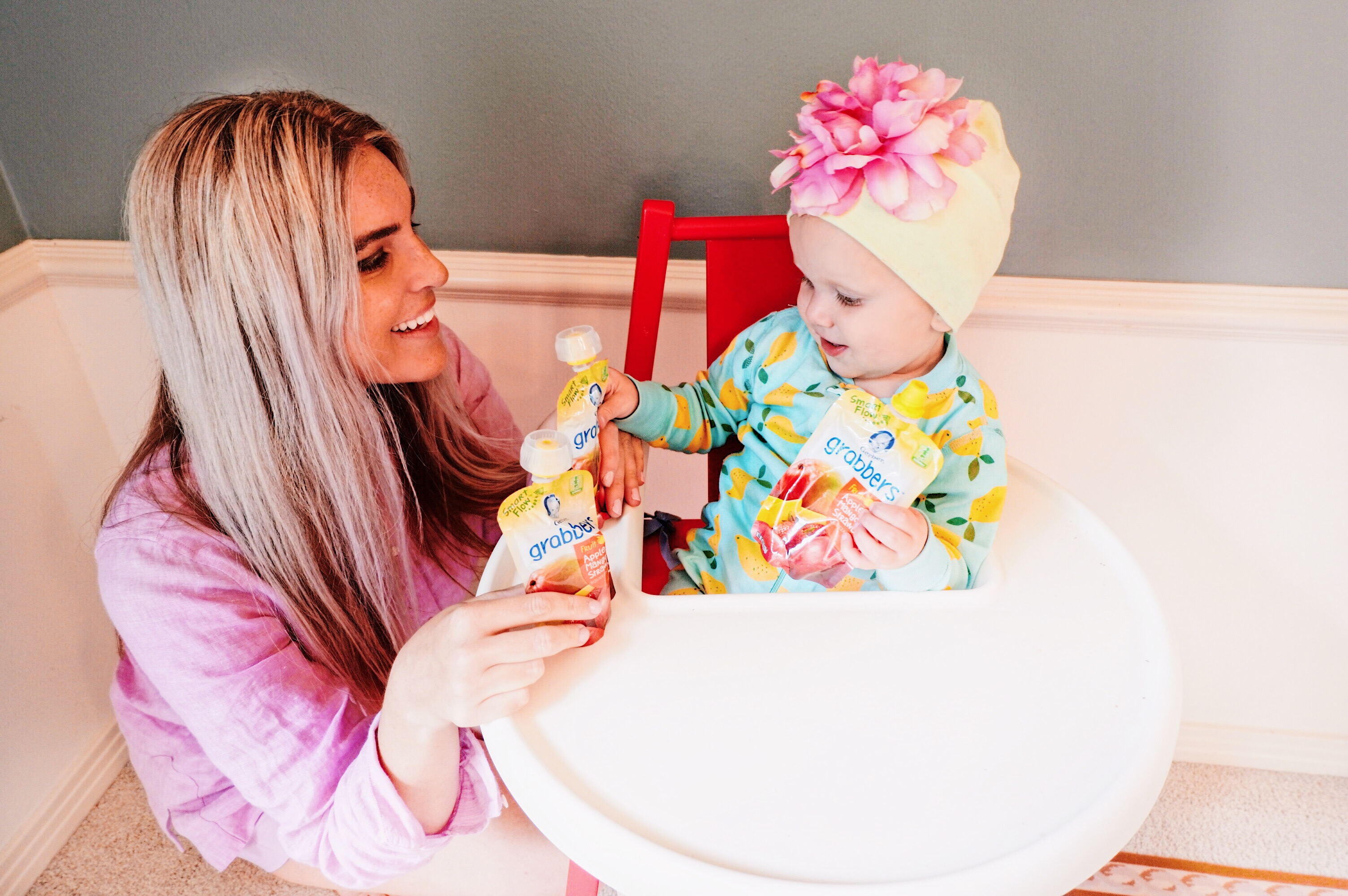 Stephany Bowman wearing JCREW violet linen tunic, Angelina Bowman wearing Hanna Anderson lemon onesie and snacking on Gerber ®️ SMART FLOW ™️ toddler pouches
