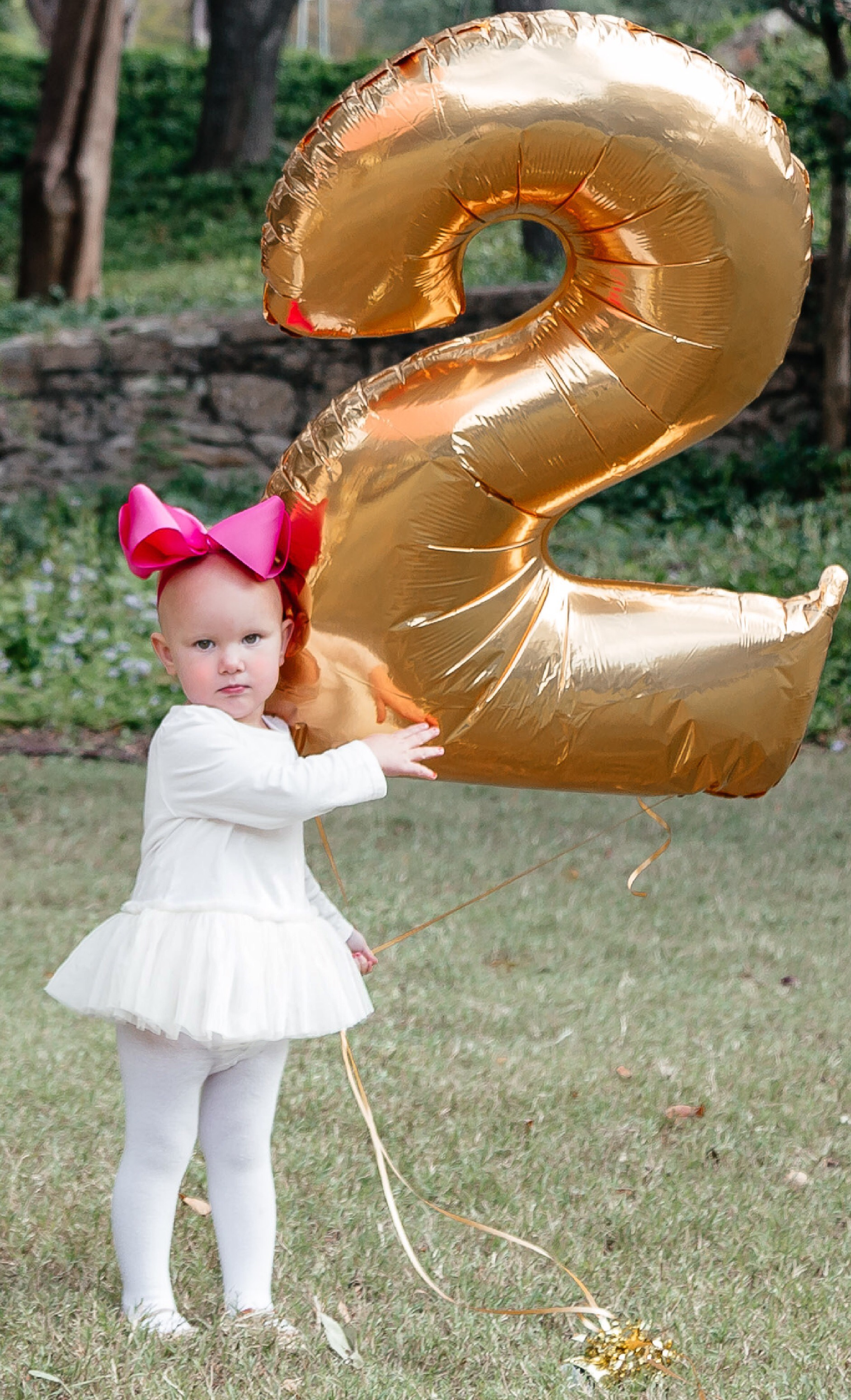 Angelina Bowman, wearing BABY GAP, celebrating 2nd birthday in cream tutu, tights and gold Mary Jane shoes