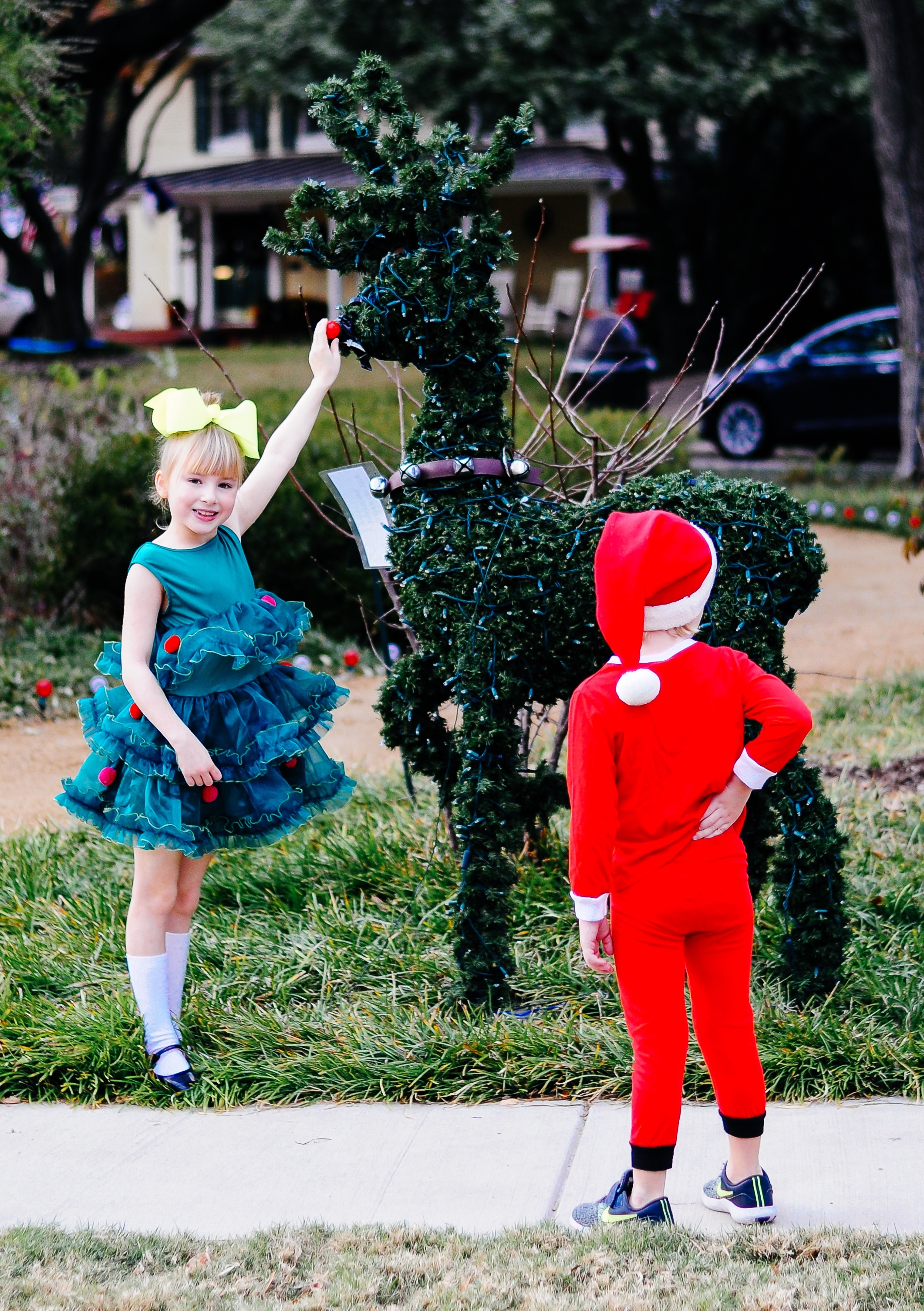 Alexander Bowman in a Santa pajama from Carter's, Santa hat from Hanna Andersson, Nike sneakers from Nordstrom, Annabelle and Angelina Bowman in matching Christmas tree dresses from H&M