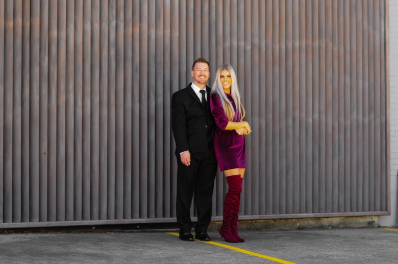 Stephany Bowman wearing ZARA sweater dress and ZARA Over the knee red boots. Michael Bowman wearing black suit and tie with white shirt all from NORDSTROM