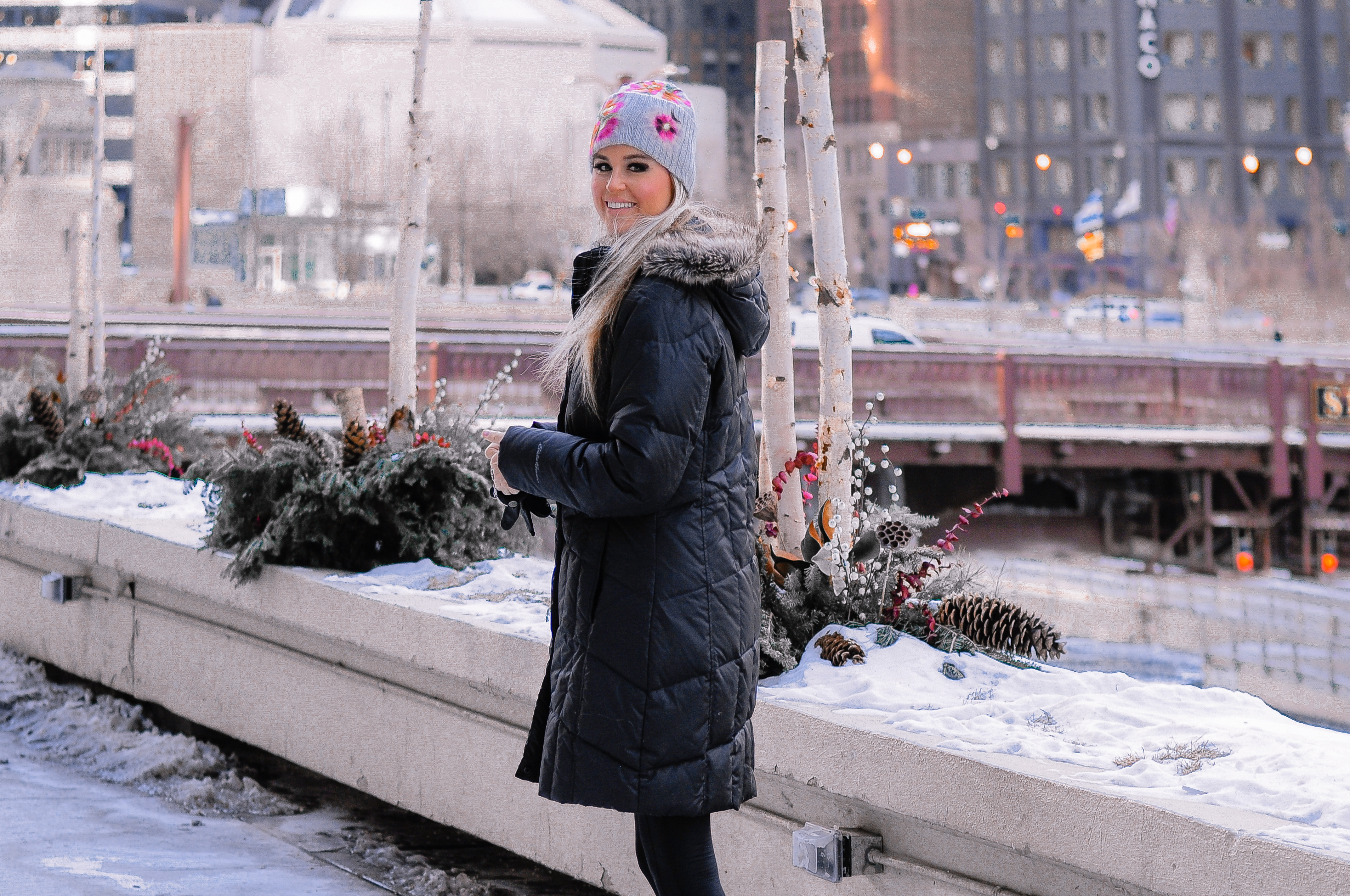 Stephany Bowman wearing an Eddie Bauer down filled winter coat in Black with Black UGG boots, and an Antrhopologie beanie in baby blue with pink flower detail, Lulu lemon leggings