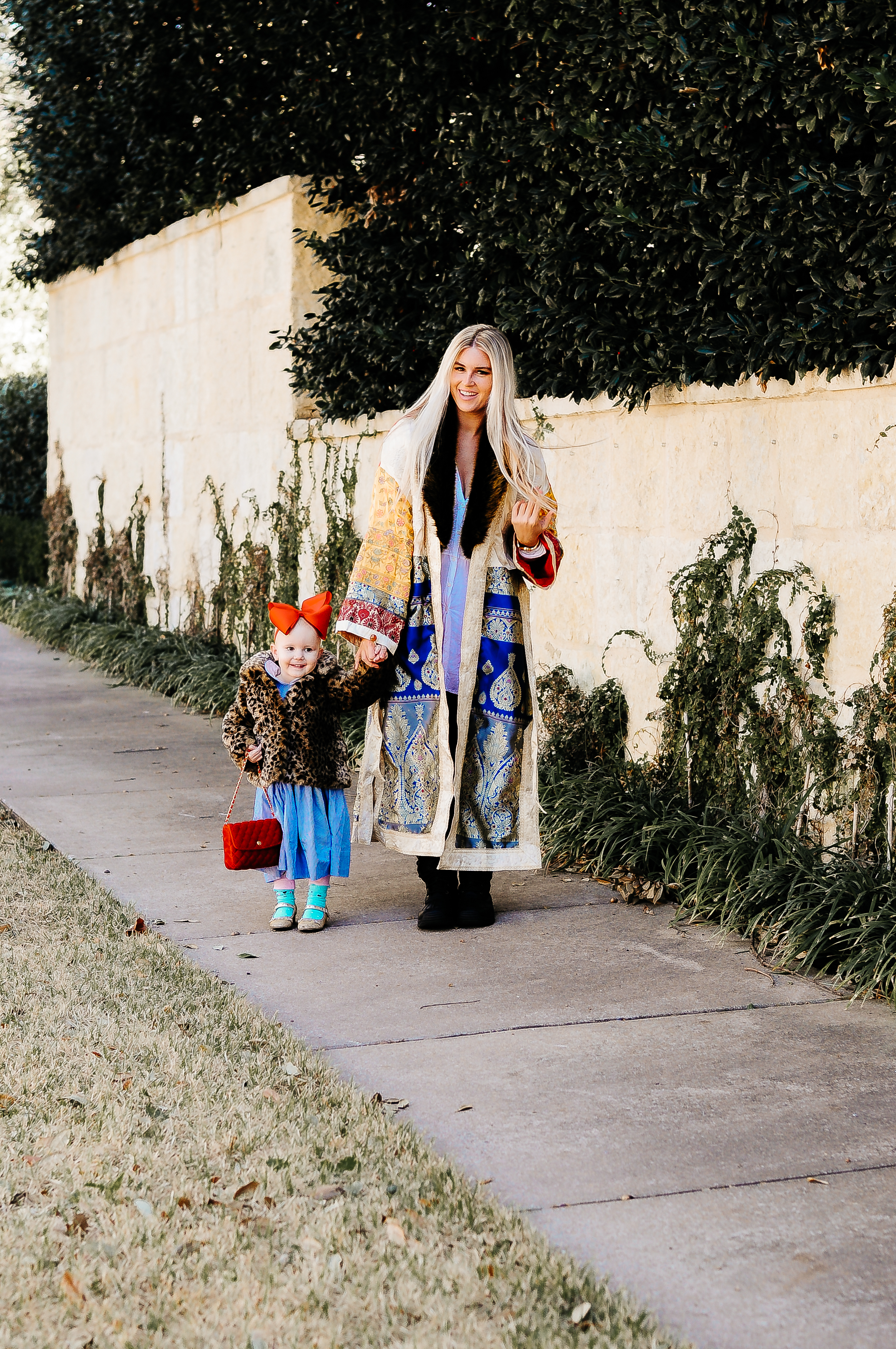 Stephany Bowman wearing FREE PEOPLE Destination Unknown Coat, Ugg boots. Angelina Bowman wearing leopard faux fur coat from OSH KOSH, Red bag from JANIE AND JACK, and red bow from ETSY